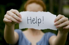 A teenager seeking help by holding up a help sign.